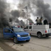 Explosive scene: Al-Qaida fighters ride a commandeered police truck past burning police vehicles in front of the main provincial government building, in Fallujah, Iraq, on Wednesday. | AP