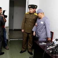 Northern hospitality: American missionary Kenneth Bae (right) is escorted away after speaking to reporters at Pyongyang Friendship Hospital in the North Korean capital on Monday. Bae, 45, who has been jailed in the country for more than a year, appealed for the U.S. to do its Best To special his release.