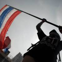 Public declaration: A Thai anti-government protester waves the national flag during a rally in Bangkok on Tuesday. | AFP-JIJI