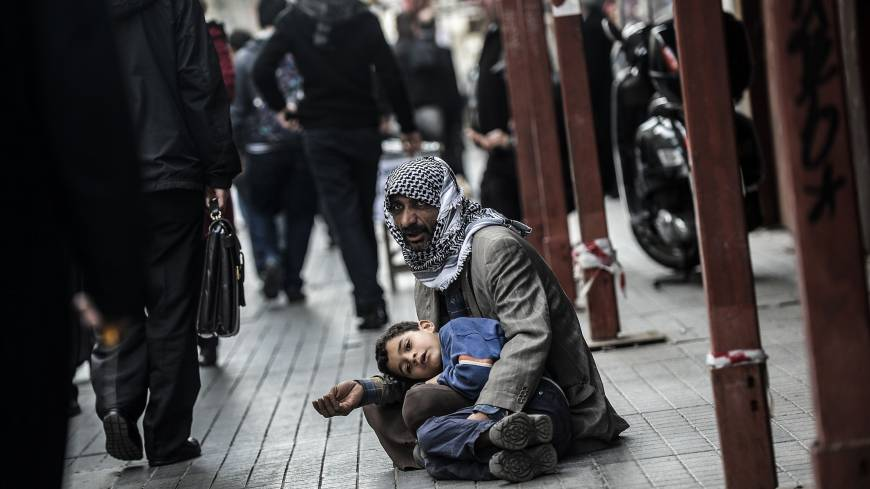 Lost souls: A Syrian man begs for money with a child in Istanbul on Tuesday.