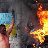 Fueling the fire: An anti-government activist warms himself and his clothes at an opposition barricade in Kiev on Tuesday. | AFP-JIJI