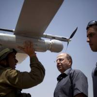 War of words: An Israeli soldier holds up an unmanned drone as part of a demonstration for Defense Minister Moshe Yaalon (center) in an urban warfare army training facility, near Zeelim, southern Israel, in July. | AP