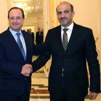 Shared interests: Syrian opposition chief Ahmad al-Jarba (right) greets with French President Francois Hollande after a meeting at the Saudi Royal Palace in Riyadh on Dec. 29. | AP