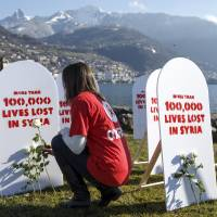 Pulling for peace: A member of movement Oxford Committee for Famine Relief (Oxfam) puts a white rose on symbolic gravestones on Wednesday, the opening day of the Geneva II peace talks on Syria, in Montreux, Switzerland. | AP