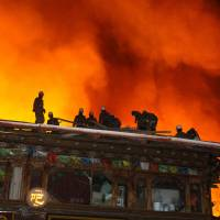 Tibetan treasure: Firefighters work to douse a raging inferno in the ancient Tibetan village of Dukezong in Shangri-La County, in southwest China's Yunnan province on Saturday. | AFP-JIJI