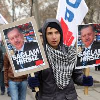Rallying point: A young man holds a placard with photos of Prime Minister Tayyip Erdogan that reads 'the perfect thief' during an anti-corruption protest in Ankara on Saturday. Tens of thousands of Turkish demonstrators took to the streets in the capital in protest against Erdogan's government, which has been rocked by a vast corruption probe. | AFP-JIJI