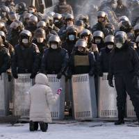 Coping a plea: A Ukrainian woman speaks as she kneels down in front of a line of riot police in Kiev on Friday. | AFP-JIJI