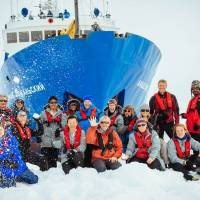 Group shot: Passengers of the MV Akademik Shokalskiy pose during a short excursion off the ship as they awaited rescue Saturday. All 52 passengers of the ship were rescued and were aboard an Australian icebreaker slowly cracking through heavy sea ice Friday after being ferried from the Shokalskiy by helicopter. | ANDREW PEACOCK/AFP-JIJI