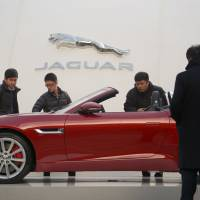 High expectations: Chinese shoppers look at a Jaguar car on display in front of a mall in Beijing on Sunday. China's economy grew 7.7 percent last year, the same as 2012, when it recorded its slowest expansion in 13 years. | AFP-JIJI