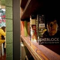 Besotted: A girl has a drink at a 'Sherlock'-themed cafe in Shanghai. The TV show has become a global phenomenon, but nowhere more than in China, where fans' devotion is so intense that the BBC says it was the first country outside Britain where the new season was shown. | AP