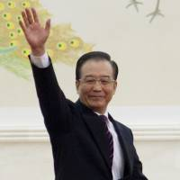 Rags to riches: Former Chinese Premier Wen Jiabao waves as he arrives for a news conference in Beijing in March 2012. | BLOOMBERG