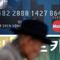 Taking credit: A pedestrian walks past an advertisement for a Citibank credit card in Seoul, South Korea,  in December 2009. Several top executives at Korean financial firms, including KB Financial Group and Lotte Card Co., offered to resign this week as a criminal probe revealed that millions of credit card holders' personal details had been compromised. | BLOOMBERG
