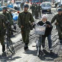Helping hand: Ground Self-Defense Force soldiers urge an elderly woman to move to higher ground during a tsunami warning on March 14, 2011, in the harbor of Soma, Fukushima Prefecture, three days after The Great East Japan Earthquake and tsunami struck the Tohoku region. | AP