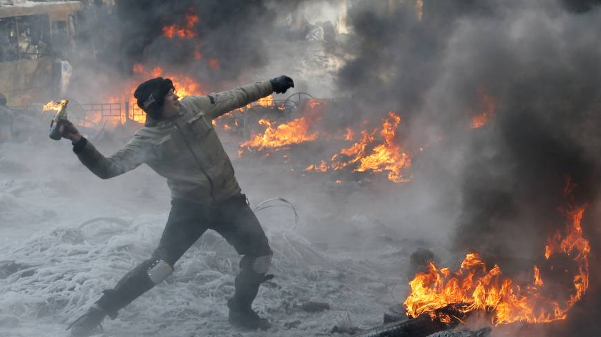 Fired up:  A protester throws a Molotov cocktail towards riot police during a clash in central Kiev on Saturday. Ukraine's Interior Ministry has accused protesters of capturing two of its officers as violent clashes have resumed in the capital and anti-government riots spread across Ukraine.