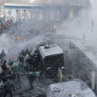 Water war: Riot police spray protesters with a water cannon during a clash in central Kiev on Saturday.   AP
