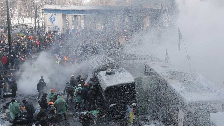 Water war: Riot police spray protesters with a water cannon during a clash in central Kiev on Saturday.