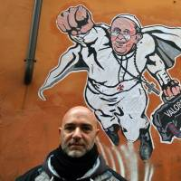 Italian artist Mauro Pallotta poses in front of his image depicting Pope Francis as Superman and holding a bag marked 'values' at the Borgo Pio district near St. Peter's Square in Rome on Wednesday. | AP