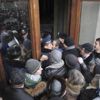 Lviving it up: Protesters break into the building of the regional governor's office in Lviv, western Ukraine, on Thursday. Tensions in Ukraine spread far from its embattled capital as hundreds of people in the city of Lviv stormed into the regional governor's office and forced him to write a letter of resignation. | AP