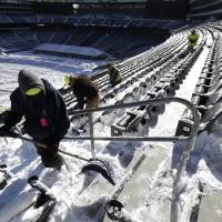 Digging in: Workers shovel snow off the seating area at MetLife Stadium in East Rutherford, N.J., on Wednesday. Super Bowl XLVIII, which will be played between the Denver Broncos and the Seattle Seahawks on Feb. 2, will be the first NFL title game held outdoors in a city where it snows. | AP