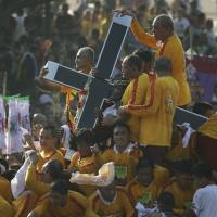 Mystical powers: Filipino Catholic devotees ride on the carriage of the Black Nazarene during an annual procession to celebrate its feast day Thursday in Manila. | AP