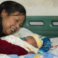 All clear: In this photo taken Dec. 12, a woman cared for her grandson who was recovering from a serious adverse reaction to a hepatitis B vaccination in a hospital in Changde, southern China. | AP