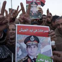False idol?: Supporters of Defense Minister Gen. Abdel-Fattah el-Sissi, head of Egypt's military, celebrate at the end of the second day of voting in a nationwide constitutional referendum in the Shubra district of Cairo on Wednesday. | BLOOMBERG