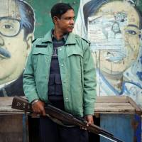 Third time's the charm: An armed policeman stands guard in front of a mural of new Bangladeshi Prime Minister Sheikh Hasina and her father and the nation's founder, Sheikh Mujibur Rahman, in Dhaka on Wednesday. | AP