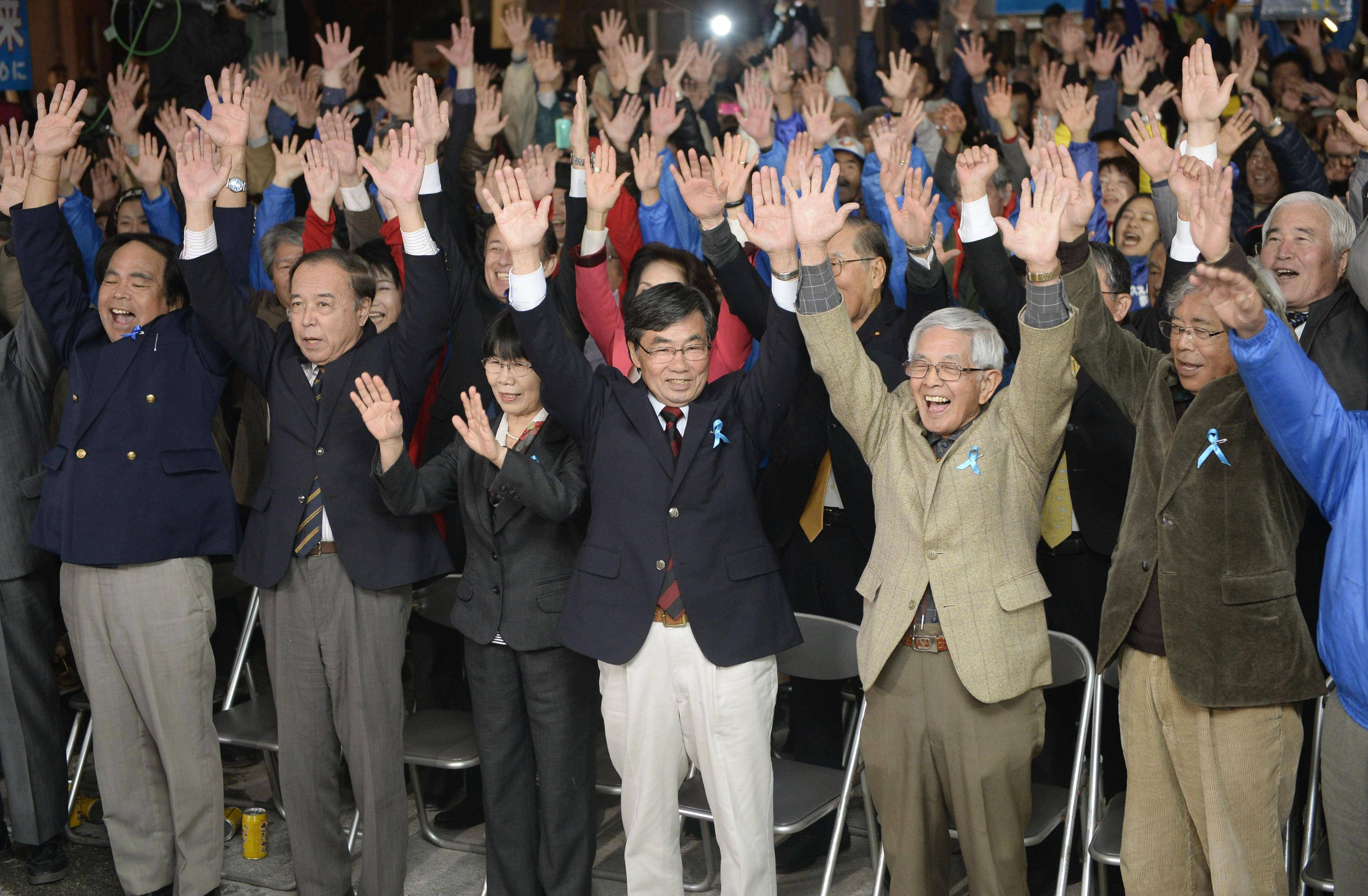 Here to stay: Mayor Susumu Inamine (center) celebrates his victory Sunday night after winning re-election in Nago, Okinawa Prefecture. | KYODO