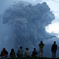 Sight to see: People watch Mount Sinabung spew volcanic materials during an eruption in Tiga Kicat, Indonesia, on Friday. The 2,600-meter volcano has sporadically erupted since September. | AP