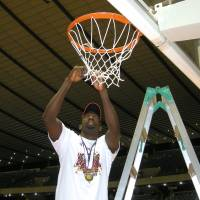 Championship tradition: Mamadou Diouf of Toshiba helps cut down the net after the Brave Thunders' 82-79 win over Toyota Motors Alvark in the Emperor's Cup title game on Monday at Yoyogi National Gymnasium. | KAZ NAGATSUKA