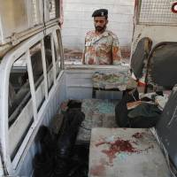 Perpetual carnage: A Pakistani security officer looks at a vehicle targeted by militants in Karachi. Police said several members of the country's security forces have been killed in separate attacks in the southern city. | AP