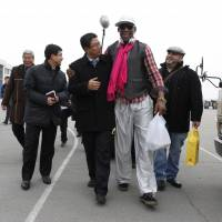 Basketball diplomacy: Former NBA basketball star Dennis Rodman (second right) walks with North Korea's Sports Ministry Vice Minister Son Kwang Ho upon his arrival at the international airport in Pyongyang on Monday. Rodman took a team of former NBA players on a trip for an exhibition game on Kim Jong Un's birthday, Wednesday. | AP