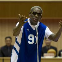 Free throw: Dennis Rodman sings the birthday song to North Korean leader Kim Jong Un, seated above in the stands, before an exhibition basketball game at an indoor stadium in Pyongyang on Wednesday. | AP