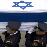 End of an era: Members of the Knesset guard carry the coffin of former Israeli Prime Minister Ariel Sharon into the parliament building in Jerusalem on Sunday. The hard-charging Israeli general and premier, both admired and hated for his battlefield exploits and ambitions to reshape the Middle East, died Saturday at age 85, eight years after a stroke left him in a coma from which he never awoke. | AP