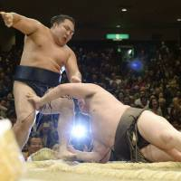 Down but not out: Hakuho (right) falls to the ground after pushing Kakuryu out of the ring in their championship playoff at the New Year Grand Sumo Tournament on Sunday. | KYODO