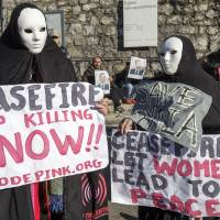 Anonymous outrage: Masked members of the movement Codepink women for peace protest near the venue of the Geneva II peace talks on Syria in Montreux, Switzerland, Wednesday. | AP