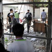 Thrower unknown: Protesters search an abandoned building for a bomber who threw an explosive device during a march by protest leader Suthep Thaugsuban and his supporters in downtown Bangkok on Friday. | AP