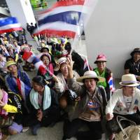 Sitting it out: Anti-government protesters cheer while blocking the entrance to a building where the office of the Department of Special Investigation is located, during a rally to close down government offices on the outskirts of Bangkok on Monday. | AP