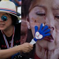 Slap in the face: A Thai anti-government protester slaps a picture of Prime Minister Yingluck Shinawatra with a clapper in Bangkok on Thursday. Yingluck government is pleading with police to arrest opposition protest leaders, who have paralysed parts of central Bangkok and threatened to take her captive. | AFP-JIJI