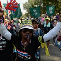 Party over?: Thai anti-government protesters march through the streets of Bangkok on Thursday. Nearly 20,000 police and soldiers will be deployed in the Thai capital this week for demonstrators' planned 'shutdown' of the city in a bid to overthrow the government. | AFP-JIJI