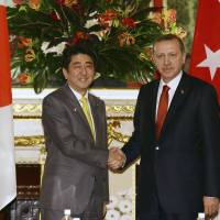 Economic dialogue: Turkish Prime Minister Recep Tayyip Erdogan is greeted by Prime Minister Shinzo Abe prior to their talks in Tokyo on Tuesday. | AP