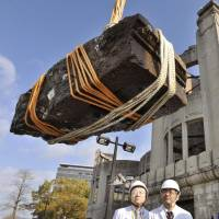 Granite rubble believed to be from the Hiroshima Peace Memorial, also known as the Atomic Bomb Dome, is lifted from the Motoyasu River on Wednesday. The chunk was apparently part of the third-floor eaves. Story: Page 2. | KYODO