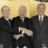 (From left) Akio Mimura, chairman of the Japan Chamber of Commerce and Industry, Hiromasa Yonekura, chairman of the Japan Business Federation, or Keidanren, and Yasuchika Hasegawa, chairman of the Japan Association of Corporate Executives, or Keizai Doyukai, shake hands during a joint news conference at a hotel in Tokyo on Jan. 7. | KYODO