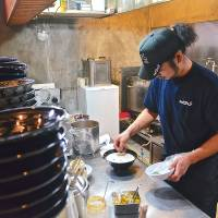 Finishing touches: A cook puts the topping on Niseko Ramen's potato-based ramen specialty.   ETHAN SALTER