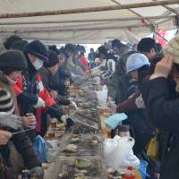 Diving in: Diners grill oysters at the Secchu Jumbo Kaki Matsuri in Anamizu.