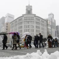 Snow begins to accumulate as pedestrians cross an intersection in Tokyo's Ginza district.  | KYODO