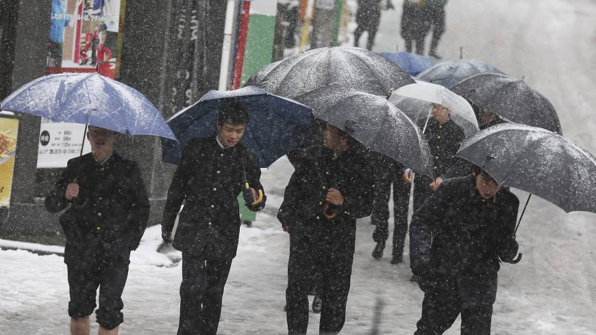 Students in school uniforms walk on a snow-covered road in Yokohama on Saturday.