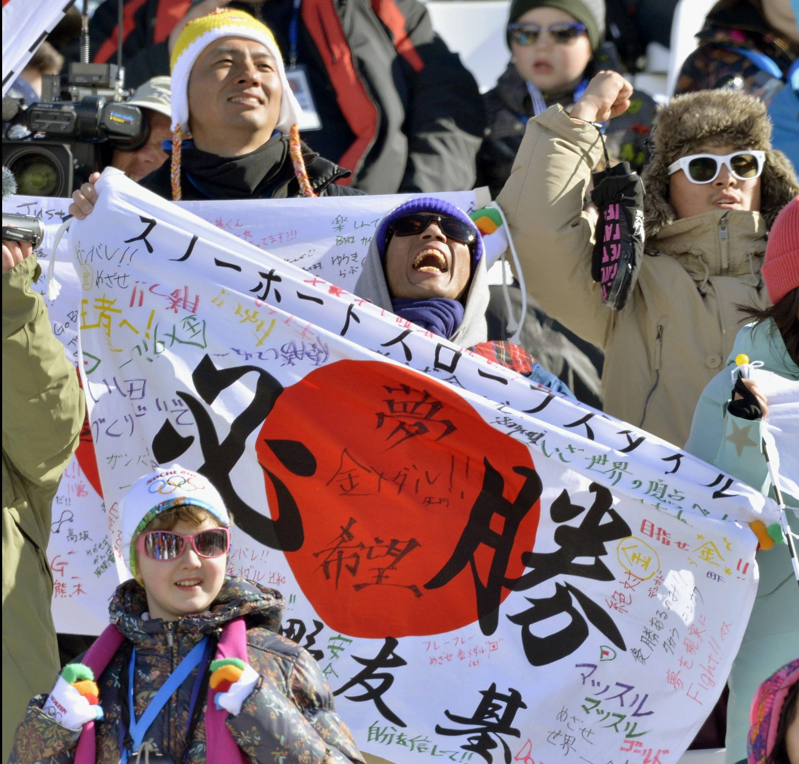 The father of Japanese snowboarder Yuki Kadano waves a signed flag during the slopestyle final Saturday.  | KYODO