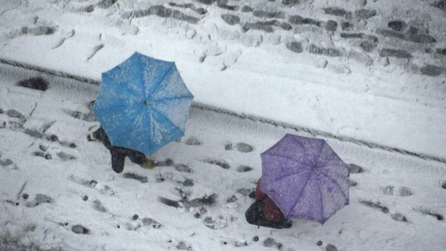 People hold umbrellas as they walk on the street covered with snow in Tokyo.  At least 27 cm accumulated, the highest snowfall in the capital since 1969.