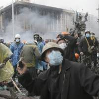 Anti-government protesters throw stones Wednesday during clashes with riot police in Kiev's Independence Square, the epicenter of the country's current unrest. | AP
